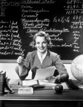 01 Jan 1950 --- 1950s smiling woman elementary school teacher sitting behind desk in front of blackboard looking at camera --- Image by © Ewing Galloway/ClassicStock/Corbis